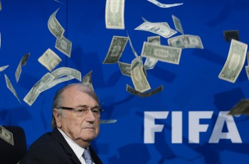 FIFA president Sepp Blatter looks on with fake dollars note flying around him thrown by a protester during a press conference at the football's world body headquarter's on July 20, 2015 in Zurich. FIFA said Monday that a special election will be held on February 26 to replace president Sepp Blatter.   AFP PHOTO / FABRICE COFFRINI        (Photo credit should read FABRICE COFFRINI/AFP/Getty Images)